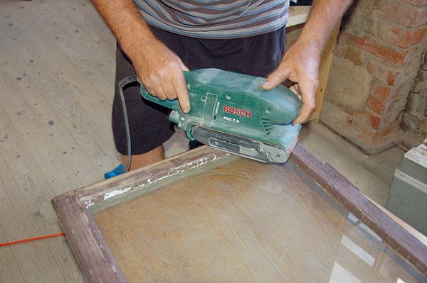 Odstránime nefunkčné časti pôvodného náteru obrúsením pásovou brúskou, oškrabaním alebo opálením.