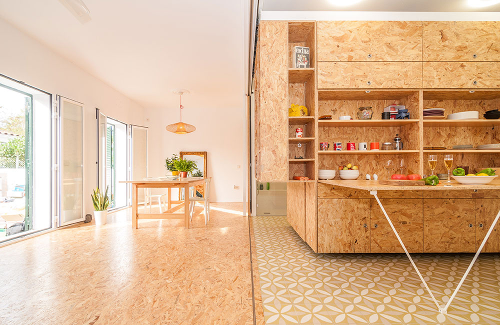 """Na podlahe nájdeme keramickú dlažbu s výraznejším vzorom, v druhej, vzdušnej časti (takmer bez nábytku) ju pokryli rovnaké drevotrieskové dosky, aké stolári použili na výrobu """"srdca"""" domu."""