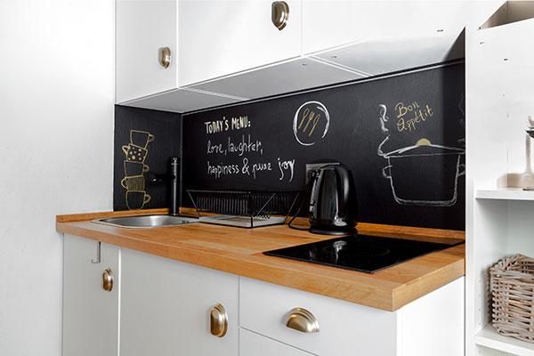 Kuchyňa s tabuľovou farbou namiesto zásteny slúži hlavne na prípravu rýchlych večerí. Avšak domáca slečna s príchodom návštevy neváha pripraviť občerstvenie. Varí totiž rada, no najradšej pre iných.