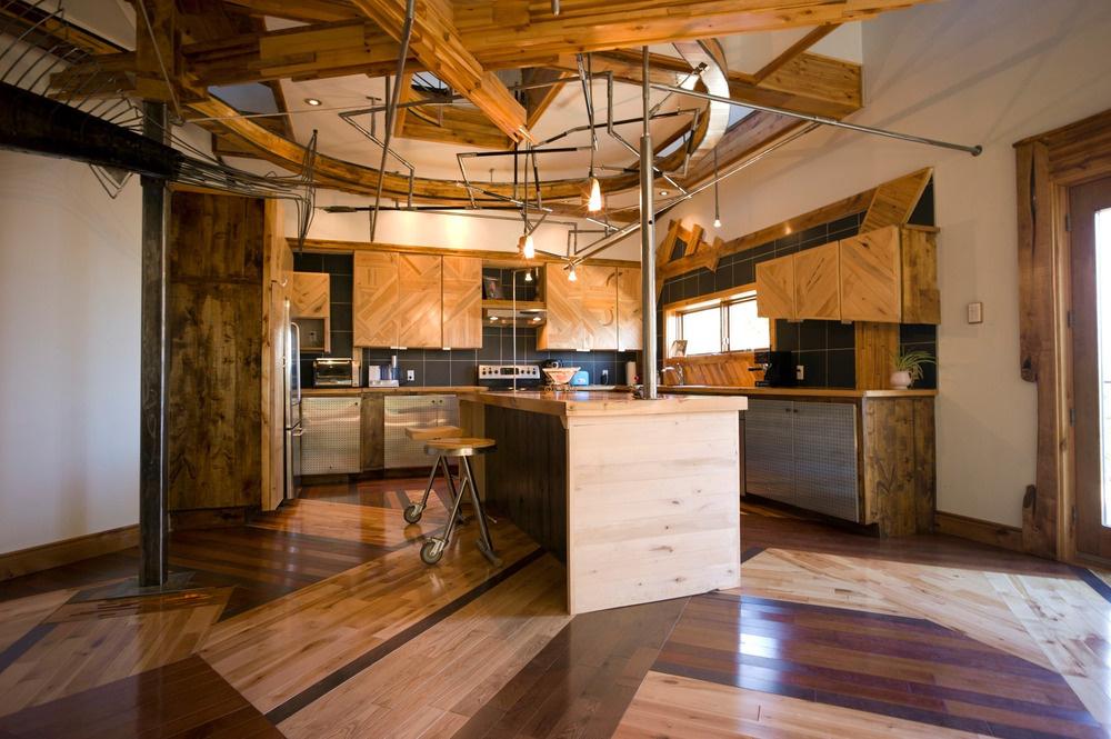 Kuchyňa vyzerá konvenčne, až na skosené hrany skriniek, netradičnú prácu s dreveným vzhľadom a spodné dvierka z perforovaného plechu.