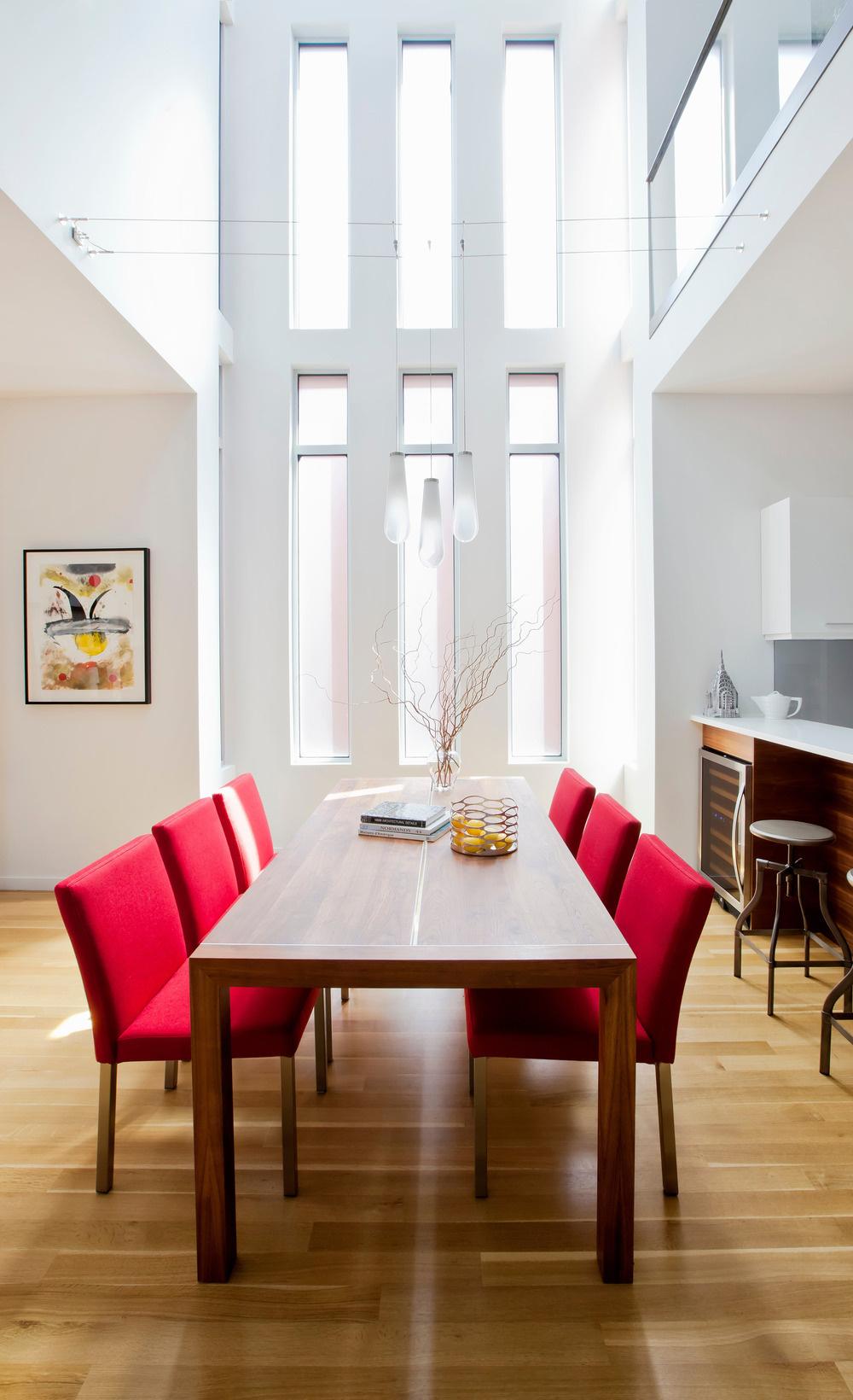 Výška obytného priestoru a dlhé vertikálne okná vnášajú do interiéru záplavu svetla. Neutrálnu farebnosť zariadenia narúša len výrazná červeň jedálenských stoličiek.