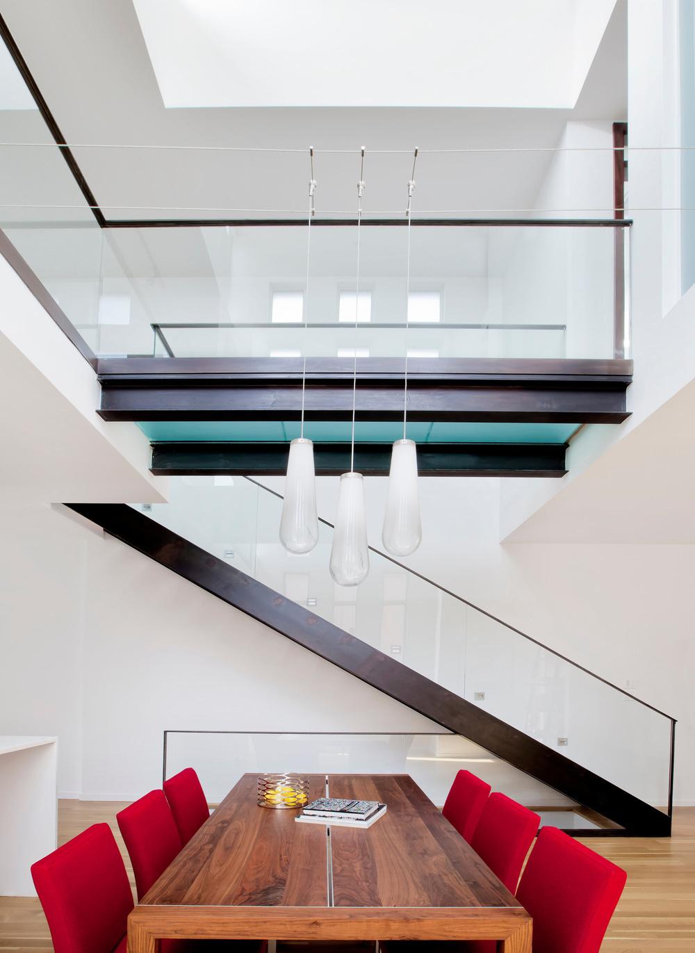 Lávka na druhom nadzemnom podlaží preklenuje otvorený priestor obývacej časti a spája dve galérie so spálňami. Luster nad jedálenským stolom je pre absenciu stropu zavesený na oceľových lankách.