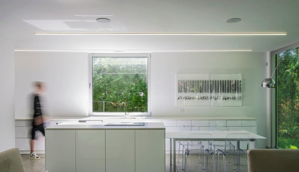 Minimalistická geometrická kuchyňa pôsobí sviežo a odľahčene, vôbec si nenárokuje pozornosť, ktorú vďaka tomu možno upriamiť na scenériu za oknami. Zeleň, zeleň a opäť zeleň.