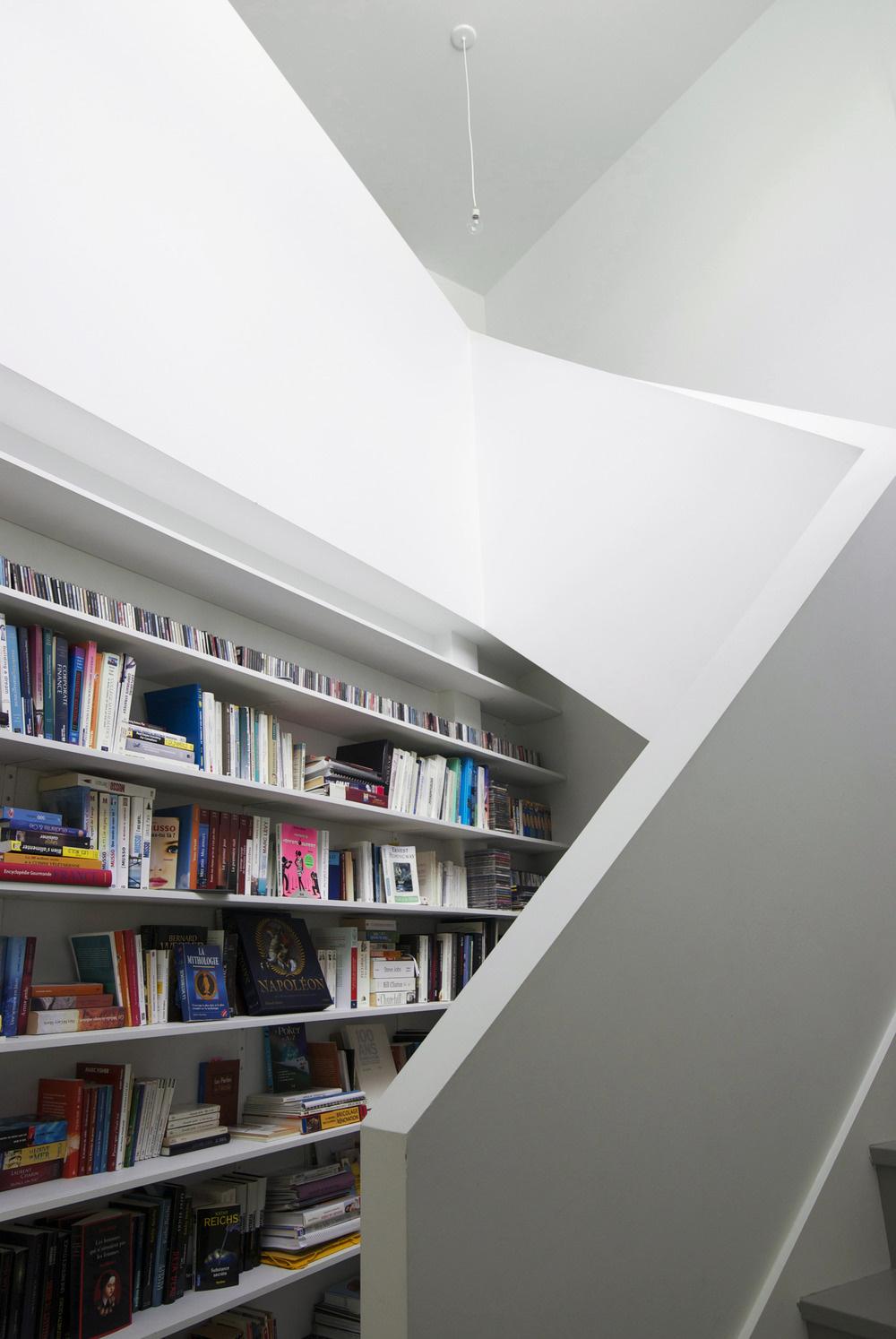 Rebelujúca stena. Knižnica plná pestrofarebných kníh získava v snehobielom priestore úplne iný význam než vo farebne veľkorysejších interiéroch.