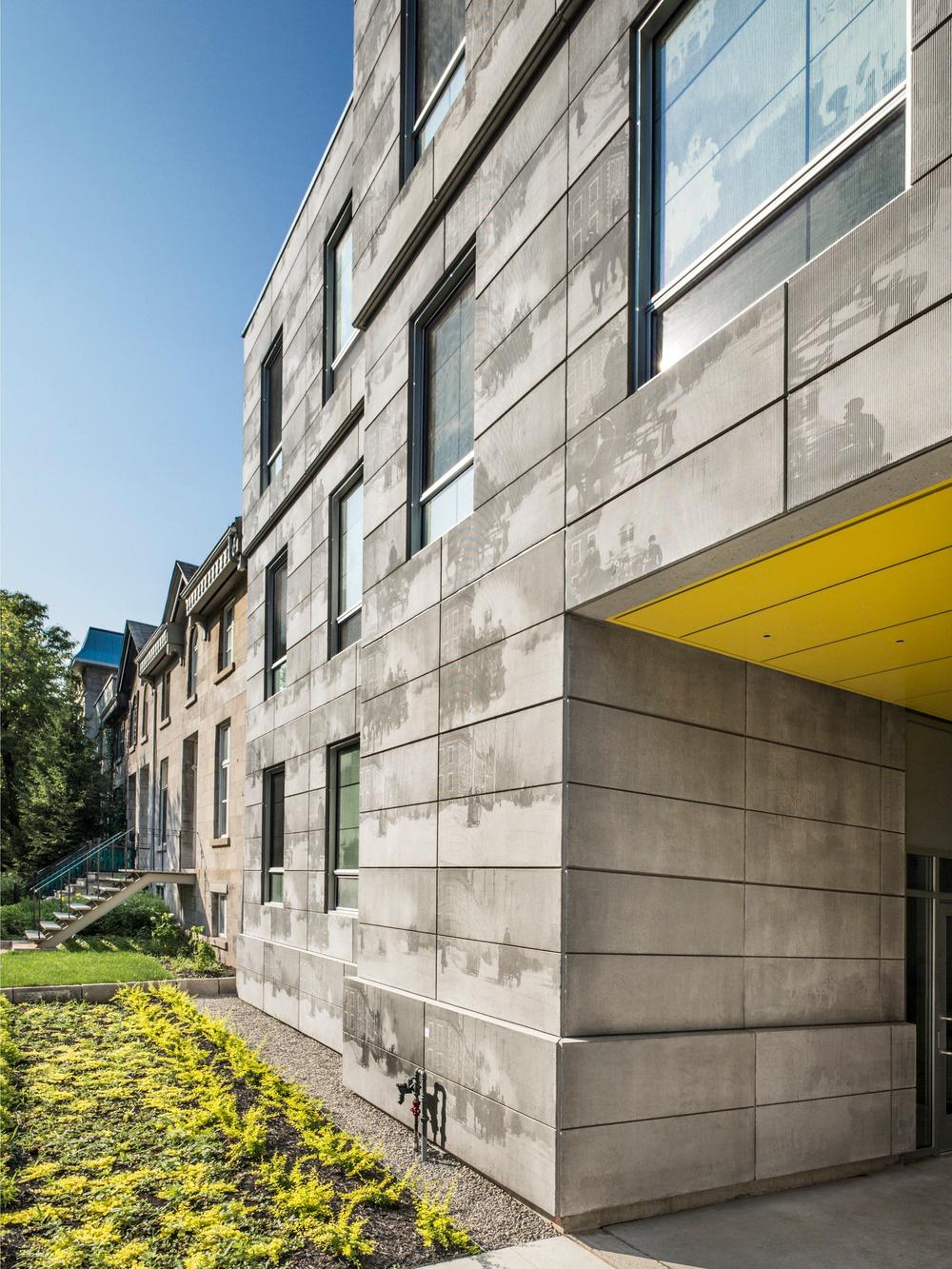 """Vstup do budovy je odkazom na typický prvok montrealskej architektúry – """"porte-cochère"""" (chránený prejazd pre konské povozy) – a poskytuje tak intímny prístup do budovy."""