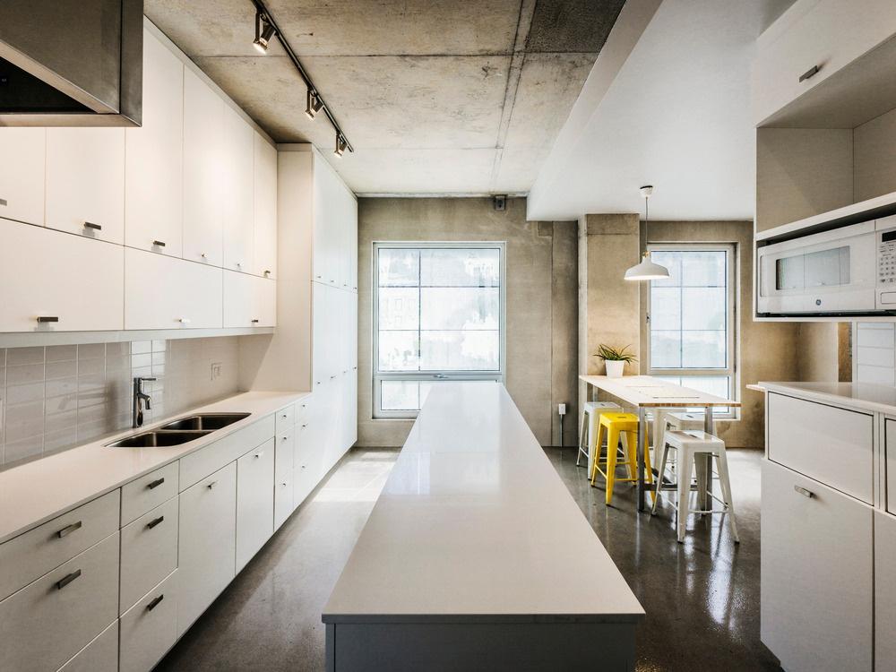 Kuchyňa je zariadená jednoducho v minimalistickom duchu, biela necháva vyniknúť surovú krásu betónových plôch. Aj tu nájdeme nenápadne zakomponovaný žltý akcent, a to v podobe barových stoličiek.