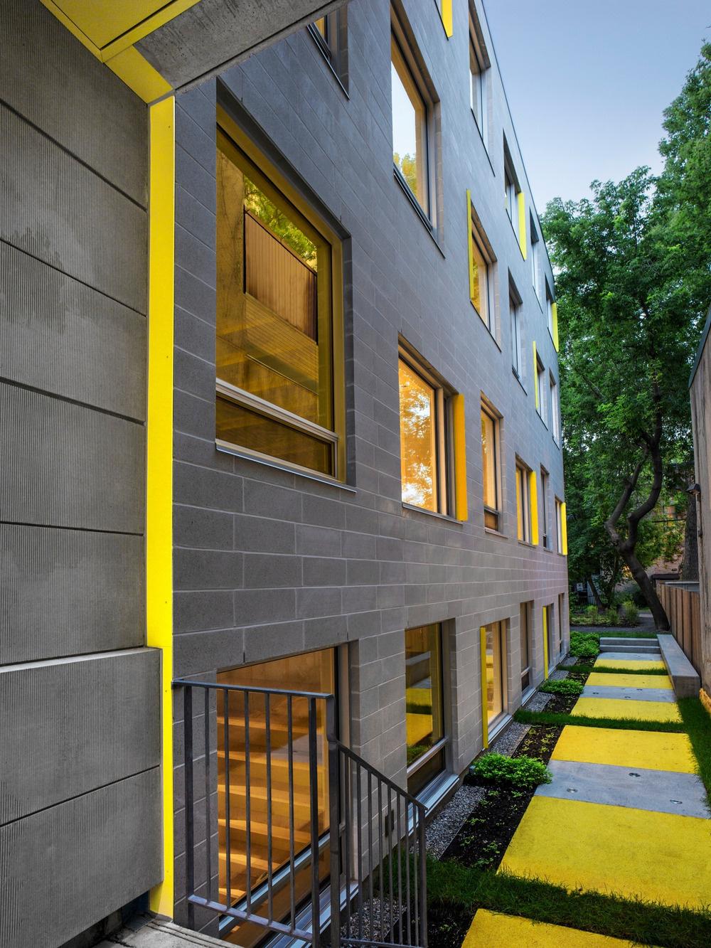 Žltý akcent na sivom pozadí sa objavuje aj v zadnej časti exteriéru: na fasáde a dvore. Strohému vzhľadu murovanej budovy tak dodáva svieži, mladistvý vzhľad, čo zodpovedá jej účelu.
