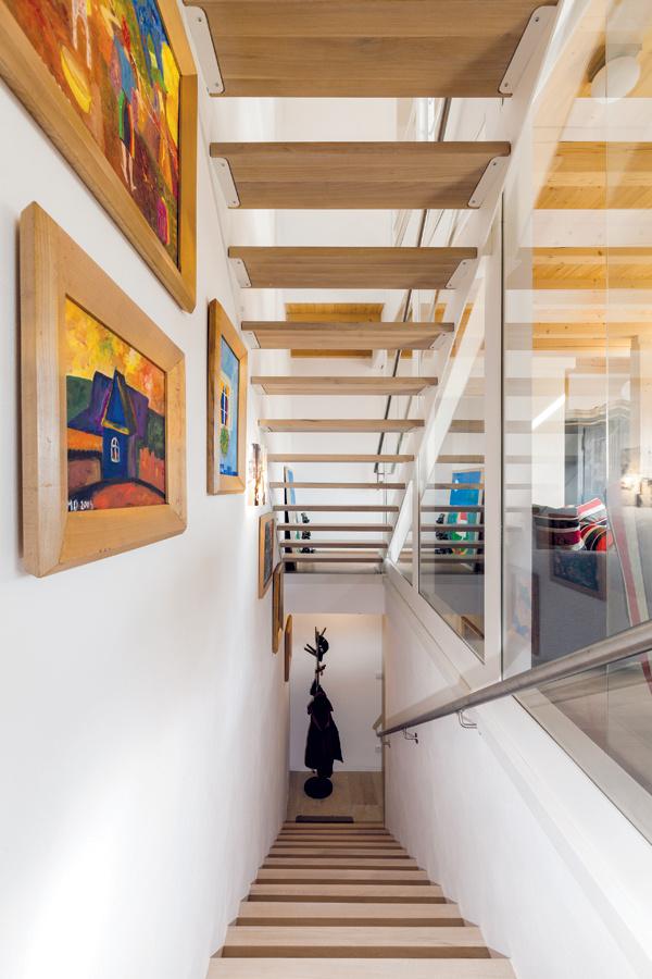 Schodisko zaberá úzky pás pri severnej stene domu a od obývačky ho oddeľuje sklená stena s posuvnými dverami – tým sa denný priestor oddelil tak, aby sa zabránilo únikom tepla, ale zároveň sa dlhá miestnosť opticky nezúžila.