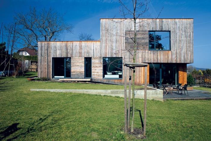 Jednoduchý a funkčný dom s drevenou fasádou dokonale kopíruje terén