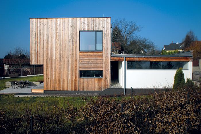 Jednoduchý dom s drevenou fasádou, ktorý sa dokonale prispôsobil terénu