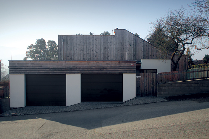 Pri pohľade z ulice pôsobí dom veľmi uzavreto. Hranicu pozemku tu čiastočne určuje blok s garážou a krytým parkovacím státím, ktorý funguje ako súčasť oplotenia.