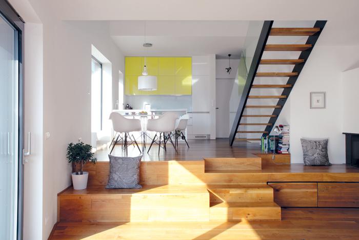 Srdcom domu je rozsiahly otvorený denný priestor s kuchyňou a jedálňou na vstupnej úrovni a s o pár schodov nižšie položenou obývačkou.