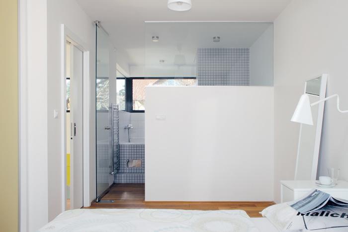 Rodičovskú spálňu na poschodí oddeľuje od kúpeľne en suite čiastočne sklenená priečka. Jeden vtipný nápad osviežil oba priestory.