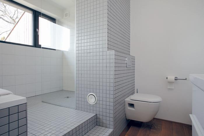 """Schodík v kúpeľni na poschodí je odrazom odlišného výškového členenia prízemia. Tu oddeľuje """"kúpaciu a sprchovaciu"""" časť kúpeľne od častejšie používanej """"toaletno-umývadlovej""""."""