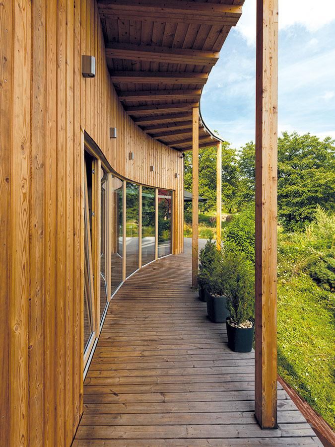 Pozdĺž celej južnej strany domu sa nachádza užšia terasa, ktorá vyúsťuje do priestrannej časti so záhradným sedením aprírodným jazierkom. Proti silnému slnku počas letných dní sú rozľahlé sklené plochy chránené presahom strechy.