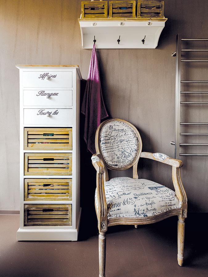 Provensálsky nádych dodávajú kúpeľni zásuvková skrinka anástenná polica, ktoré kombinujú biely náter apatinované drevo. Sviežim akcentom je drevené kreslo so vzorovaným poťahom. Poslúži na odloženie oblečenia alebo aj na relax.