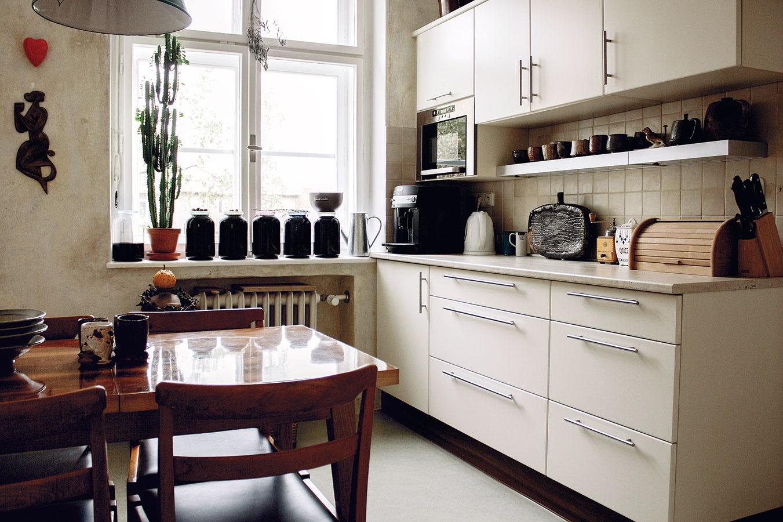 Keramické kachličky vizuálne prepájajú kuchynskú linku soriginálnou škrabanou omietkou, sktorou dokonale farebne ladia.