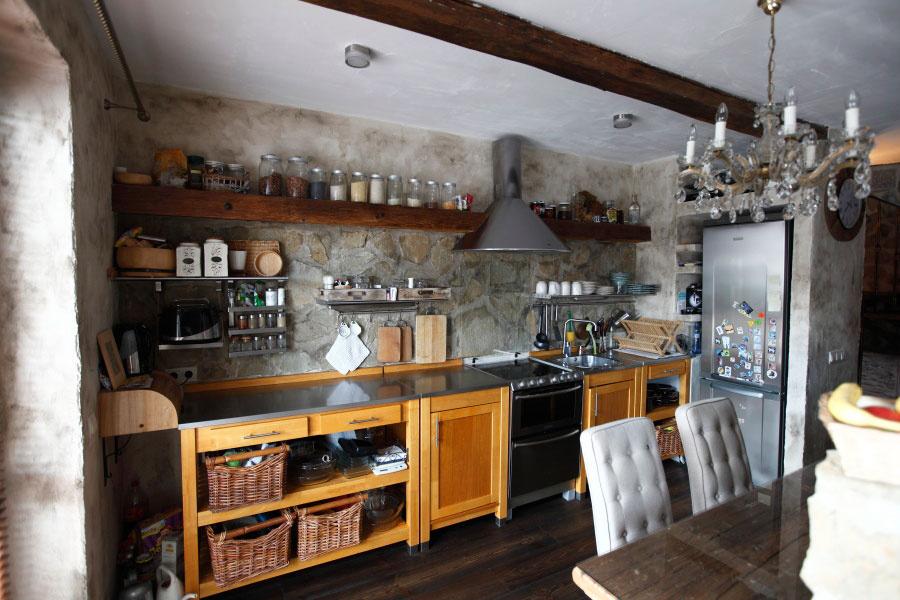 Priama kuchynská linka svymurovaným priestorom na chladničku vyrobená zo svetlého masívu kontrastuje so zvyšným, prevažne tmavým drevom. Kuchynskú zástenu tvorí obklad zpieskovca, ktorý nájdete aj pri schodisku alebo vkúpeľni.