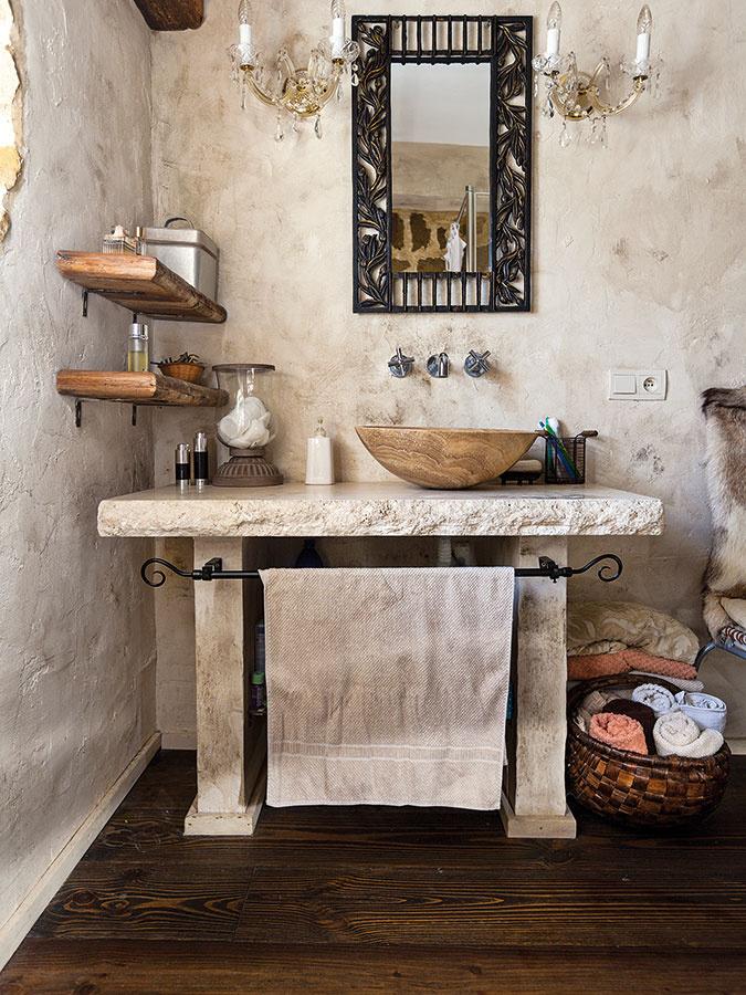 Centrálna kúpeľňa na prízemí má podobne ako tá na poschodí prírodného ducha. Skrinky nahradil murovaný stolček skameninovým umývadlom. Jednoduché drevené police ponúkajú priestor na nevyhnutnosti, uteráky sú štýlovo zrolované vprútených košoch.