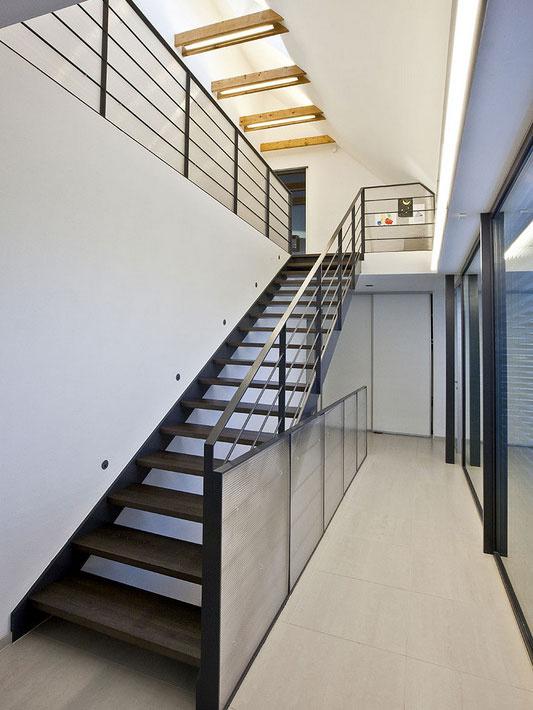 Strešné okná privádzajú denné svetlo do veľkej chodby, ktorá je dominantným priestorom v najstaršej časti rodinného domu.
