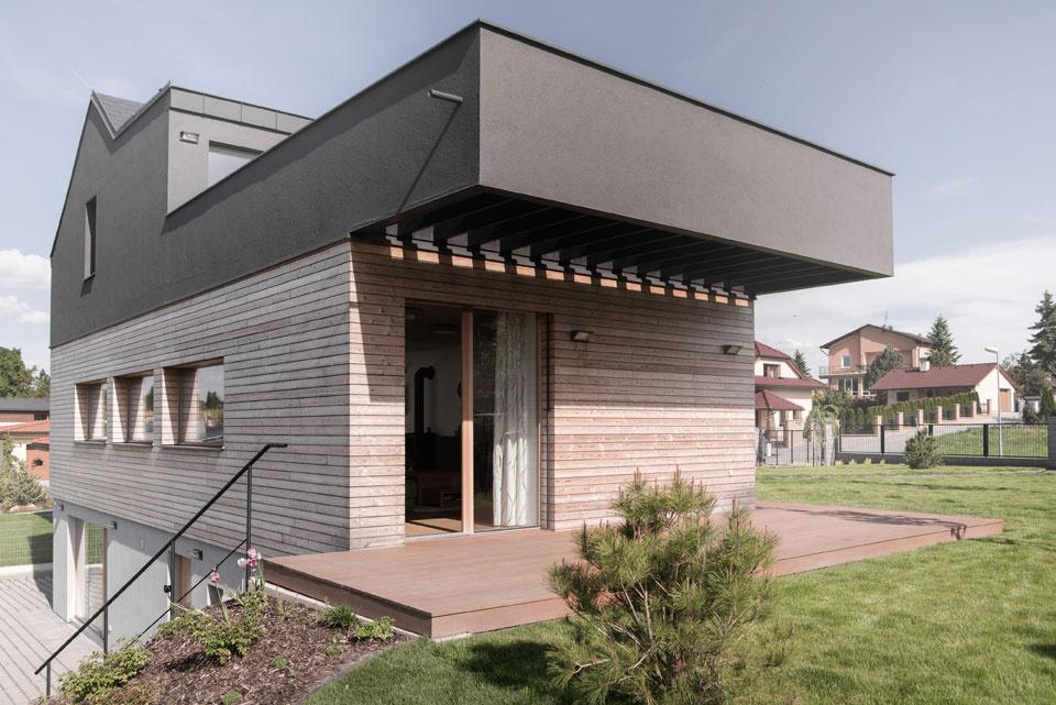 Terasa s dreveným povrchom, ktorý je použitý i na fasáde tohto poschodia.