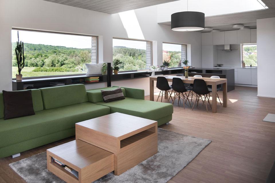 Veľká miestnosť v sebe spája kuchyňu, jedáleň a obývačku. Namiesto obrazov tu majú okná s výhľadom na krajinu a blízke lesy. Tlmená farebnosť zariadenia korešponduje s okolitou prírodou.