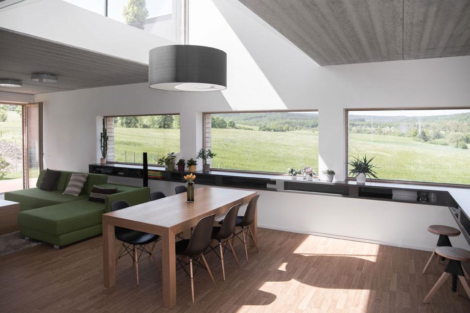 Nad jedálenským stolom svetlá výška dosahuje dve poschodia. Toto riešenie zdôrazňuje dôležitosť miesta pri stretávaní rodiny.
