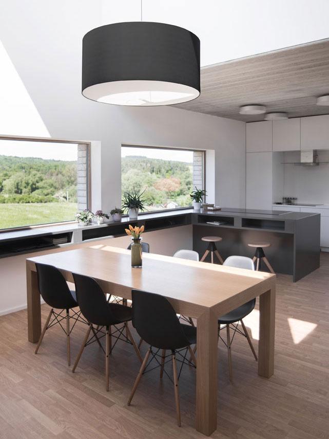 Nad stolom je zavesený výrazný, ale jednoduchý luster, ktorý ladí s celým vybavením interiéru.