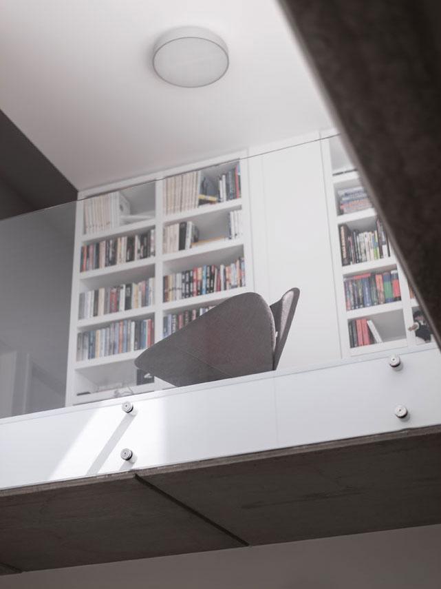 """Majitelia môžu v dome komunikovať v """"horizontálnej i vertikálnej"""" rovine. Priestor venovaný zabudovaným knižniciam hovorí o záujmoch obyvateľov."""