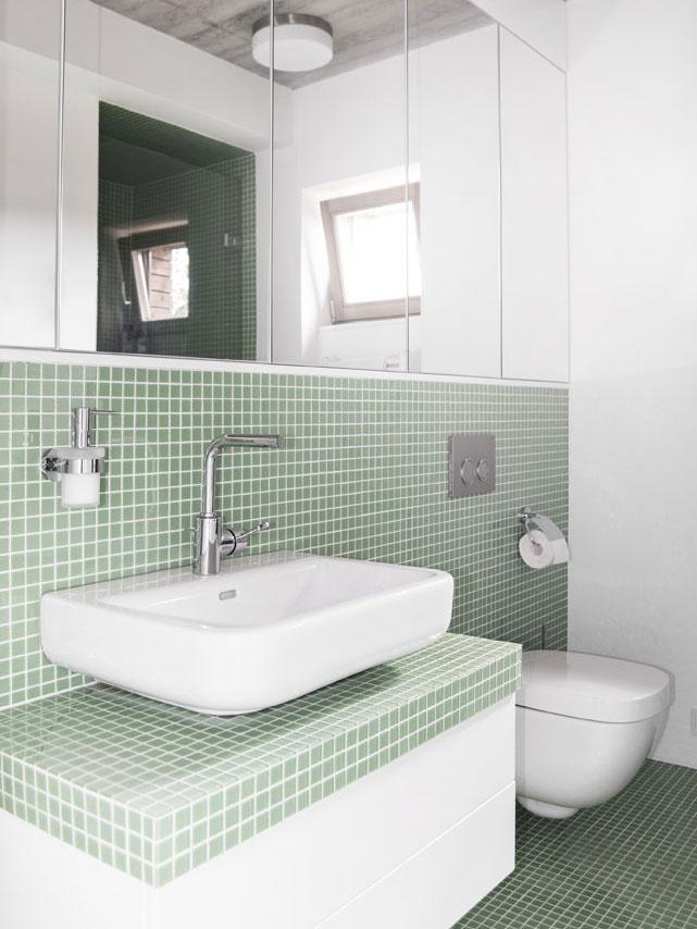Svetlá a striedma kúpeľňa zaujme kombináciou veľkých zrkadiel a malého formátu mozaiky. Obľúbenosť kúpeľňových mozaík stále rastie, tu je aplikovaná jednoducho a funkčne v mätovom odtieni.