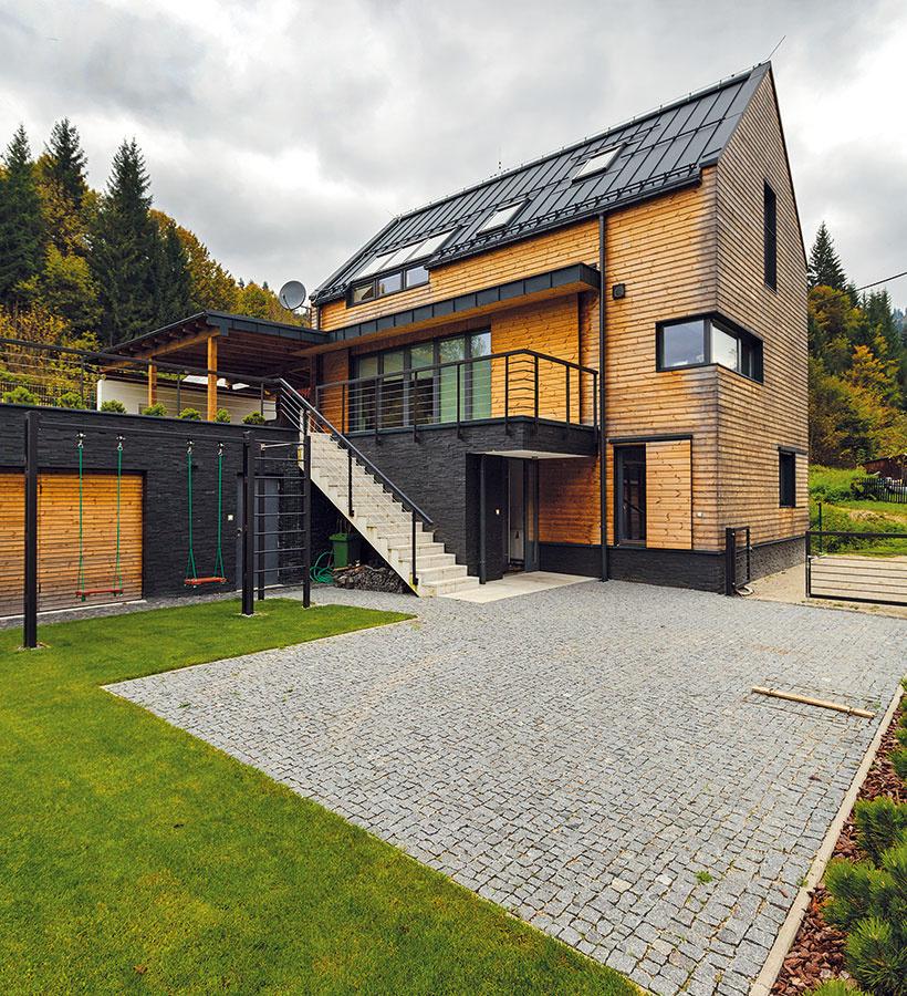 Do zložitého terénu s prevýšením viac než 3 m navrhli architekti dvojpodlažný dom sčiastočne zapusteným obytným prízemím aobytným podkrovím pod sedlovou strechou. Vstupuje sa doň zo spodnej terasy, horná terasa sa využíva ako rekreačná aobytná záhrada.