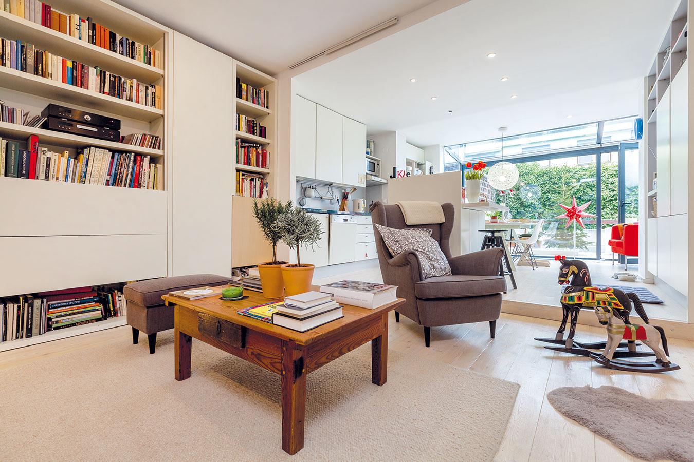 Veľkorysá denná časť prepája obývaciu izbu skuchyňou ajedálenskou časťou, ktoré sú mierne vyvýšené. Aby sa priestor využil čo najfunkčnejšie, nábytok si nechali majitelia vyrobiť na mieru. Do prevažne bieleho interiéru vnášajú farebnosť doplnky aživot rodiny.