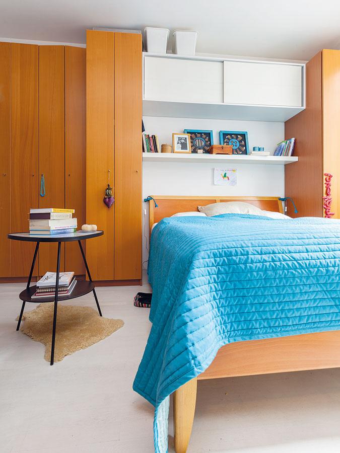 Vrodičovskej spálni je príjemným spôsobom skombinované drevo sbielou ažiarivou modrou farbou. Stolík je domovom knižiek, ktorých je vcelom byte neúrekom, anahrádza aj ten nočný.