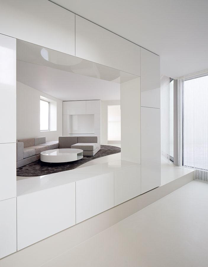 Vinteriéri vládnu elegantné čisté línie apoužité farby sú blízke tým zexteriéru – jemné odtiene sivej. Dom ponúka množstvo podnetov apocitov, ktoré sa menia počas dňa iročných období, preto bola podľa architektov určitá striedmosť pri zariaďovaní namieste. Hranaté tvary vobývacej izbe vkusne zjemňujú okrúhly stôl ikoberec.