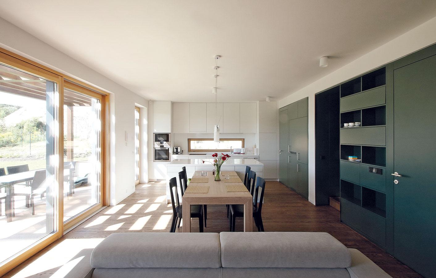Interiér zodpovedá celkovej koncepcii, ktorá zahŕňa striedmosť, eleganciu ajednoduchosť. Na bielu kuchynskú linku nadväzujú robustnejší stôl zo svetlého dreveného masívu avpriestore výrazne pôsobiace tmavé stoličky.