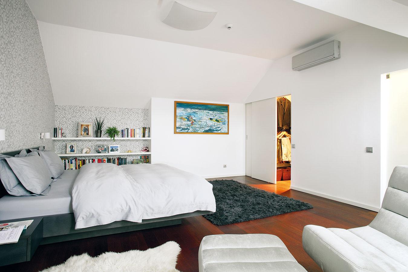 Vspálni manželov zdobí steny dekoračná tapeta srastlinným motívom, príjemnú drevenú podlahu ešte zútulňujú kožušiny akoberec.