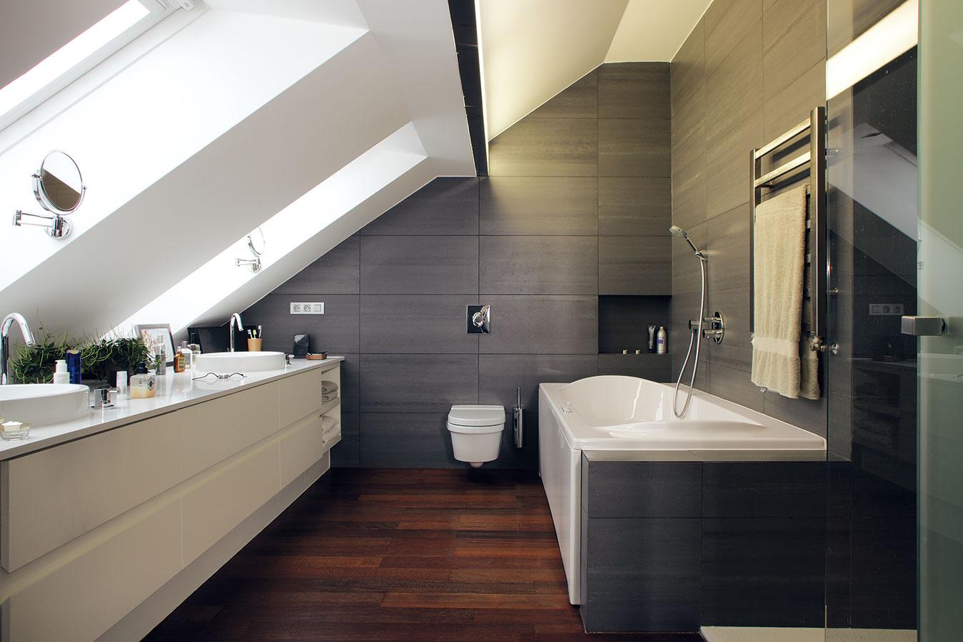 """Sivo-bielu kombináciu na drevenom """"základe"""" nájdeme ivrodičovskej kúpeľni. Poskytuje skutočne kráľovské pohodlie: dve umývadlá, veľkú vaňu aj sprchovací kút."""