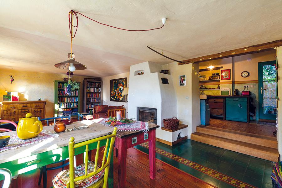"""Na rozľahlú dennú miestnosť nadväzuje kuchyňa v pristavanej časti domu. Vďaka veľkému otvoru bez dverí a jednotnému štýlu vybavenia má človek pocit voľného, otvoreného priestoru, časť kuchyne pritom ostáva decentne skrytá """"za rohom""""."""