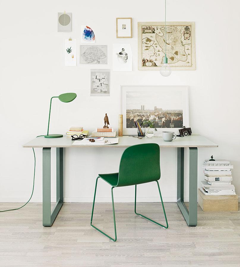 Vznamení zelenej. Pri výbere farebnosti sa pokojne riaďte svojimi preferenciami. Zelená je farbou sviežosti arovnováhy,vpracovni má preto svoje opodstatnenie. Rovnako ako vtomto kútiku snábytkom astolnou lampou značky Muuto. (Predáva www.kabinet.sk)