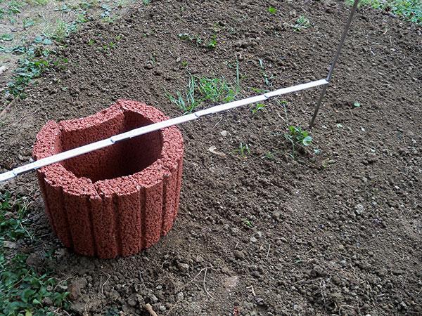 Vyrovnáme terén, ktorý upravíme dusaním. Vytýčime si stred jahodovej pyramídy. Podľa vonkajšieho polomeru prvéhokruhu osadíme prvú tvarovku. Na stanovenie polomeru použijeme špagát alebo meter.