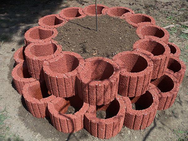Vnútro kruhu vyplníme zeminou. Zeminu upravíme ručným dreveným dusadlom a následným polievaním vodou so záhradnou hadicou. Zemina musí byť pri tvárniciach zarovno uhladená a utlačená. Pre prípadné sadanie zeminy odporúčame však vyspádovať zeminu  smerom hore od tvárnic k stredu kruhu.