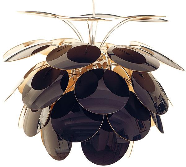 """Strapec diskov lampy Discocó vnáša do interiéru neodolateľný náboj optimizmu. Je dielom dizajnéra Christopha Mathieua, ktorý oňom začal uvažovať niekedy vroku 1997 na základe dôkladných štúdií nepriameho svetelného toku podľa Poula Henningsena. Delikátnu konštrukciu plastových """"tanierikov"""" sústredených okolo lesklého kovového jadra sa mu však podarilo vyrobiť až vroku 2008. Od 684 €, Marset, predáva Smart Light"""