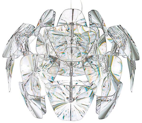 """Hravá lampa Hope sa vo svojom dizajnérskom nápade rozchádza spodobnými """"artičokovými"""" modelmi. Spoločnú má snimi len konštrukciu dômyselne poskladaných lupienkov, namiesto nepriameho však ponúka opticky filtrovaný priamy tok svetla. Dizajnéri Francisco Gomez Paz aPaolo Rizzatto pri jej návrhu využili vlastnosti fresnelových lúp – plastových šošoviek svrúbkovaným povrchom, na ktorých sa svetlo triešti aláme viskrivom """"ohňostroji"""". Od 830 €, Luceplan"""