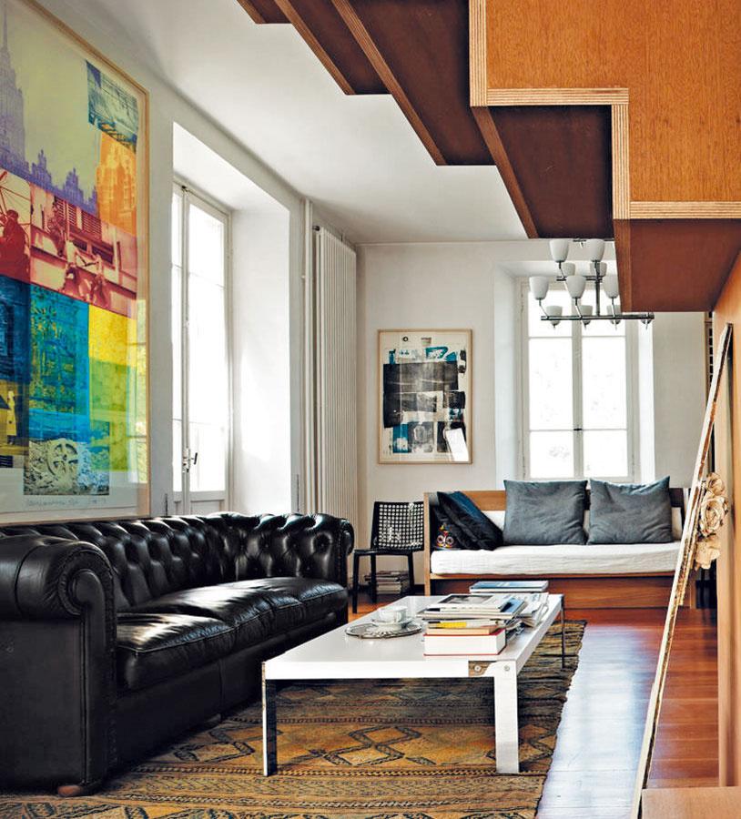 Čierna koža, drevo a funkčnosť sú typické pre pánsky interiér. Obrazy ho však zjemnia a dodajú mu aj umelecký nádych.