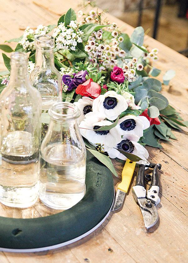 Materiál anáradie  aranžérska hmota na živé rastliny vtvare venca  záhradné kliešte nôž 3 sklenené fľaše svodou rôznych veľkostí  biele, červené afialové anemonky  ostatné doplnkové rastliny (eukalyptus, kalina, chamelaucium, limonka, populus)