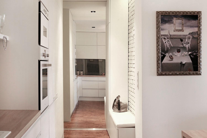 Rôzne funkčné priehľady v byte dopĺňa iluzívny priehľad, ktorý vznikol umiestnením zrkadla na celú stenu priamo pri vstupe do bytu. Šatník je zakomponovaný do zostavy tvoriacej s kuchyńou jeden celok.