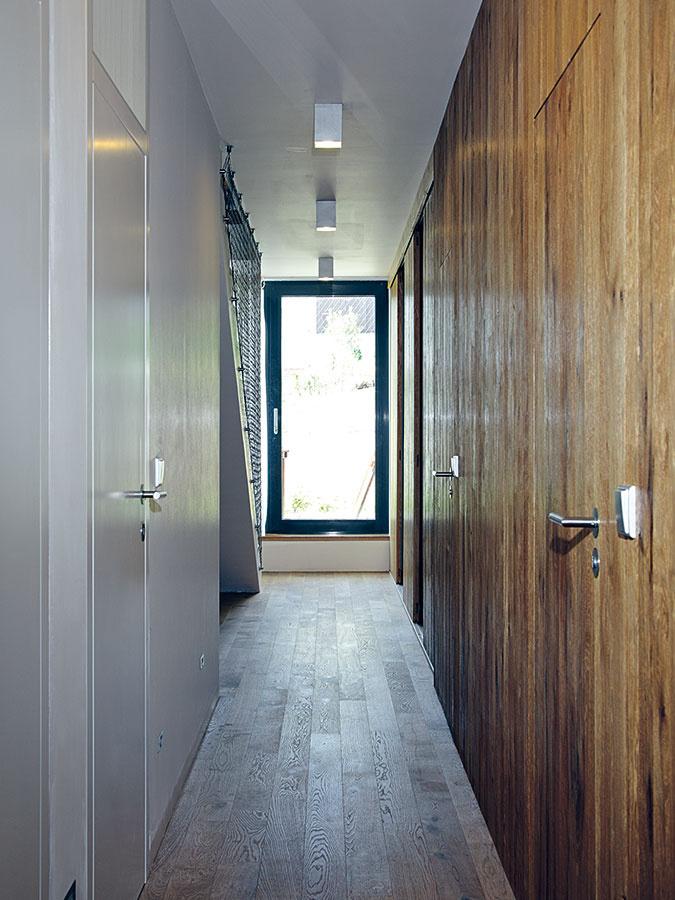 Za stenou z olejovaného duba sa v chodbe na najnižšom podlaží ukrýva kúpeľňa a toaleta, a tiež priestor na technické vybavenie domu (kotol, práčka, vysávač a pod.).