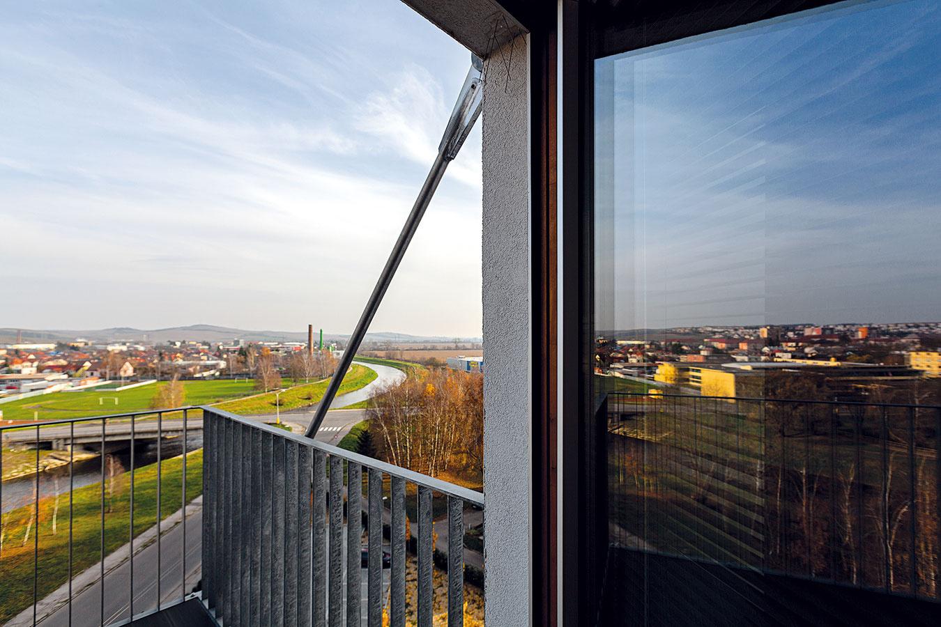 Jednoduchá biela fasáda pôsobí veľmi príjemne aprimerane. Efektne ju oživujú zavesené oceľové balkóny, na ktoré sa vďaka ich veľkorysým rozmerom (2× 2 m) pohodlne zmestí stôl so štyrmi stoličkami.