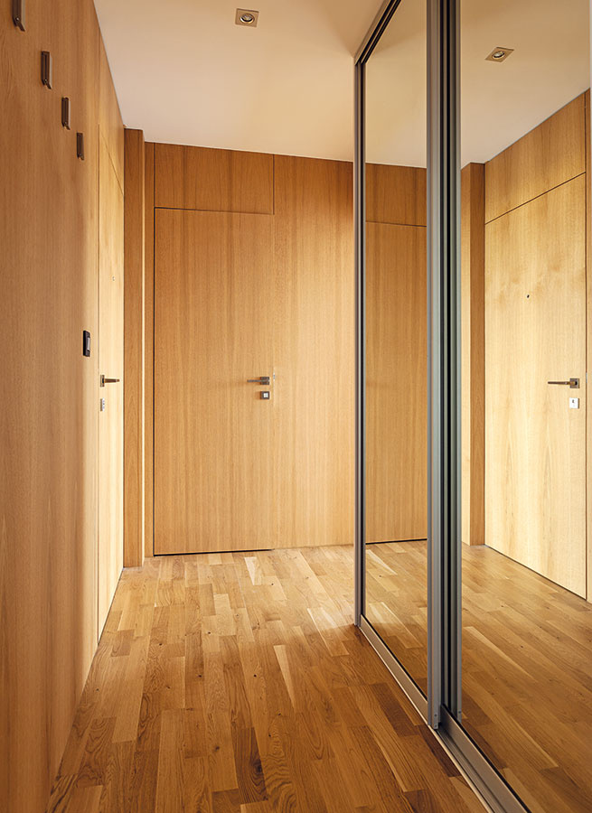 """Zabudované """"vychytávky"""". Aj pri vstavaných skriniach sa myslelo na detaily – či už estetické (napríklad bočné strany sú bez viditeľných spojov), alebo praktické. Pomocou zrkadiel napríklad opticky rozširujúchodbu, inde sa zas za čistými plochami dverí skryli rozvody, čím sa priestor upratal. Vo vstavaných skriniach vchodbe sa počítalo aj smiestom na práčku vrátane potrebných rozvodov."""