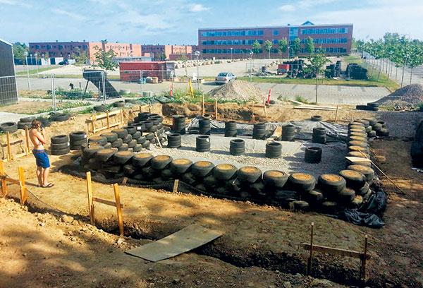 """Hlavným stavebným materiálom študentského tímu boli ojazdené pneumatiky, zktorých sú súvisle """"vymurované"""" tri obvodové steny. Prvý rad pneumatík je uložený 1,4 m pod terénom atvorí základy domu."""